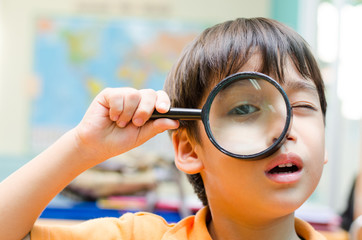 Little boy looking trough a binoculars map background
