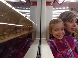 Mother and daughter reflected in a train window