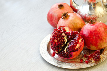 Ripe pomegranate on a silver moroccan plate copy space