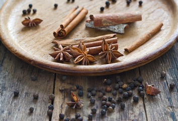 Cinnamon, anise and piper nigrum on wood plate