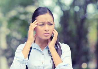 unhappy woman stressed having headache outside park background