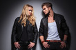 Hot fashion couple leaning on a grey wall
