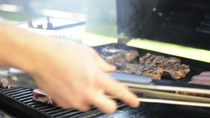A man grills lamb chops on the outdoor barbeque