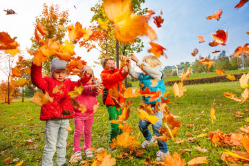 Active group of children play with flying leaves