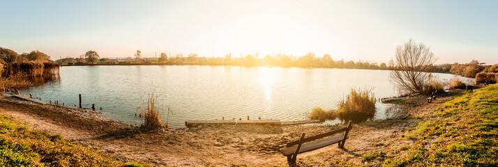 Beautiful sunset over the lake. Panoramic view.