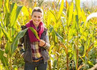 Portrait of happy young woman standing in cornfield