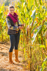Full length portrait of happy young woman in cornfield