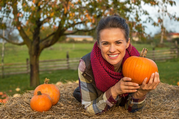 Portrait of happy woman laying on haystack and holding pumpkin