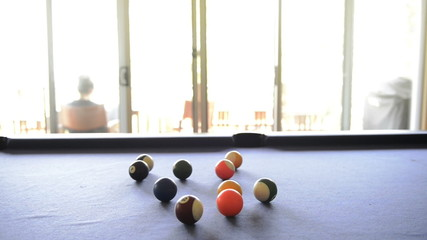 A person cheats and steals a billiard ball from the pool table i