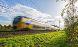 Passenger train moving at high speed in sunlight - 72539564