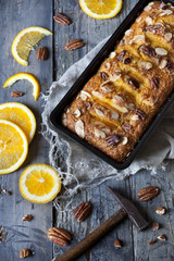 citrus plumcake with pecan walnuts on mold on table with hammer