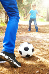 Happy dad and son playing football in the park
