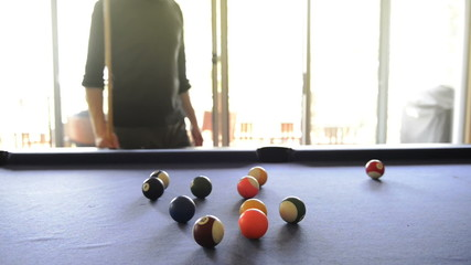 A man walks behind pool table looking for the best shot
