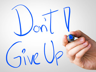 Don't Give Up hand writing with a blue mark