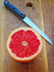 Half of grapefruit on wooden plank