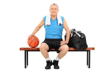 Mature man with basketball sitting on a bench