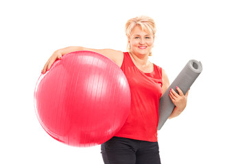 Mature woman with a fitness ball and an exercise mat
