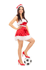 Girl in Santa costume with football under her foot