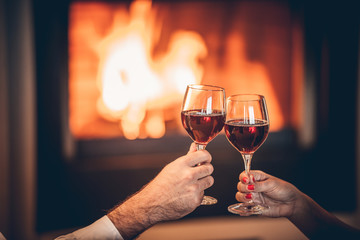 glasses red wine and fireplace