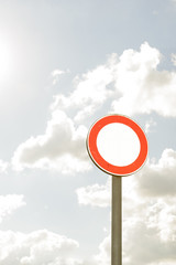 round road sign with white area and sky in the background