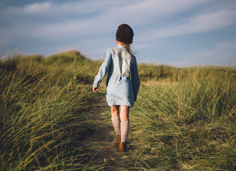 Young girl walking on a trail to the beach.