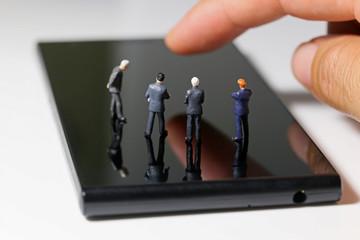 スマートフォンと4人のビジネスマン