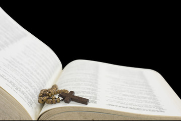 Cross of rosary beads resting against open bible.