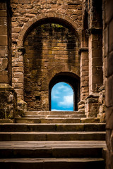 Stone castle steps and arched doors leading to blue sky