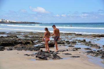 pareja caminando por la playa de famara en lanzarote