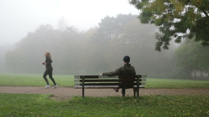 man sitting on bench in park and thinking about his life