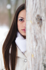 Portrait of the beautiful girl in winter forest