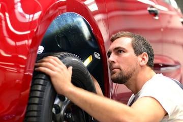 KFZ Mechaniker kontrolliert Reifen und Fahrzeug in d. Werkstatt