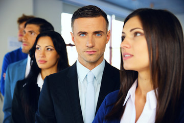 Group of a young serious businesspeople standing