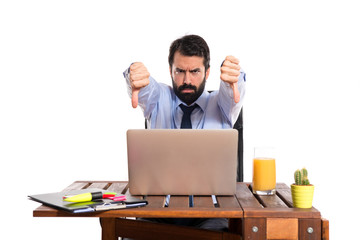 Businessman in his office  doing a bad signal