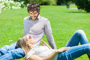 Young happy couple relaxing on the grass