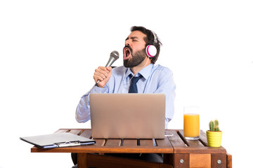 Businessman in his office singing