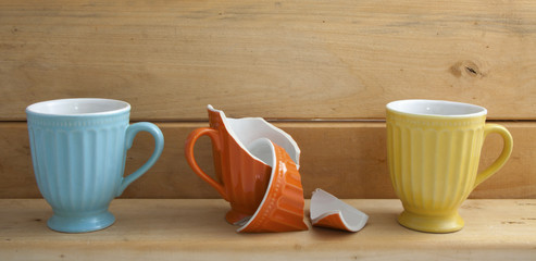 Three cups on wooden shelf