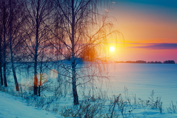 Beautiful winter sunset over snowy field