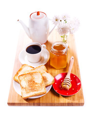 breakfast with toast bread, honey and coffee on wooden board