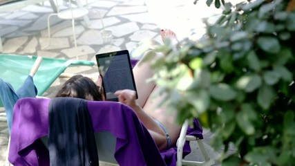 woman at pool reading on tablet