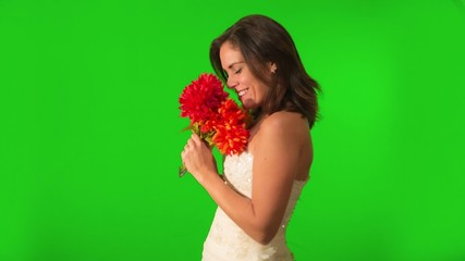 Happy bride looking at ring and holding flowers, on Green Screen