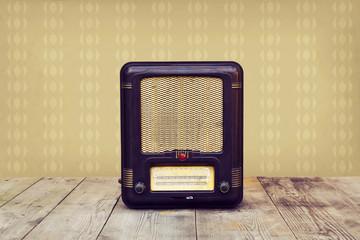 Retro radio on a wooden floor over vintage wallpaper