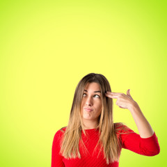 Young girl making suicide gesture over  green background