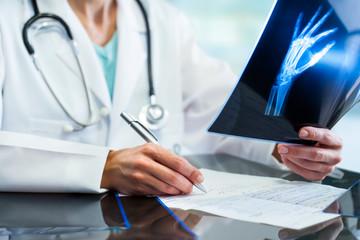 Medical practitioner writing down prescription.