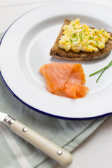 Smoked salmon close-up with scrambled eggs with chives