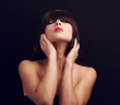 Beautiful glamour woman touching short hair on dark background