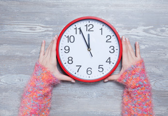 Female hands holding clock on a table.