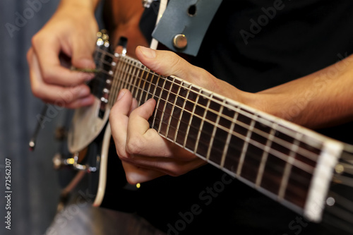 electric guitar close-up with fingers playing it - 72562307
