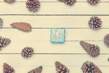 Gift box and and pine cone on a wooden table.
