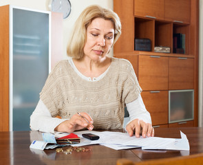 serious mature woman calculating the family budget